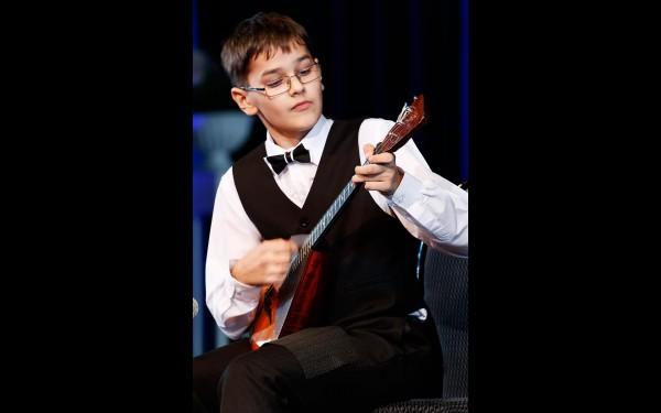 Десятилетний Иван Попов из Усть-Илимска получил новенькую балалайку, он исполнил для гостей композицию Даниила Крамера «Танцующий музыкант»