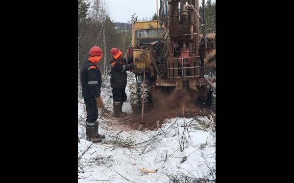 С помощью передвижной установки рабочие бурят скважину, куда впоследствии будет заложена взрывчатка. Бур проникает в подземную толщу через грунт и твердые доломиты.