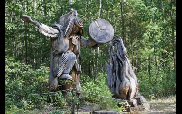 У входа в Ангарскую деревню им. О. Леонова гостей встречает деревянная фигура шамана