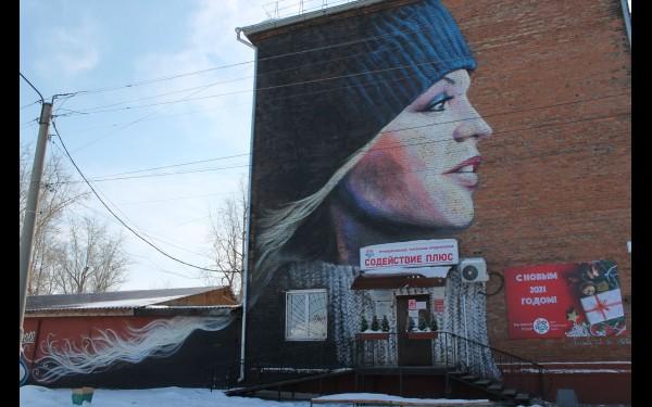 Если отойти подальше, то увидишь, что рисунок волос девушки плавно перетекает с фасада дома на другое здание.