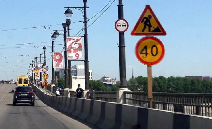 Дорожные знаки, предупреждающие о сужении дороги и необходимости снизить скорость, строители оставили на мосту до окончания работ, несмотря на то, что в будни здесь ничего не напоминает о реконструкции теплотрассы