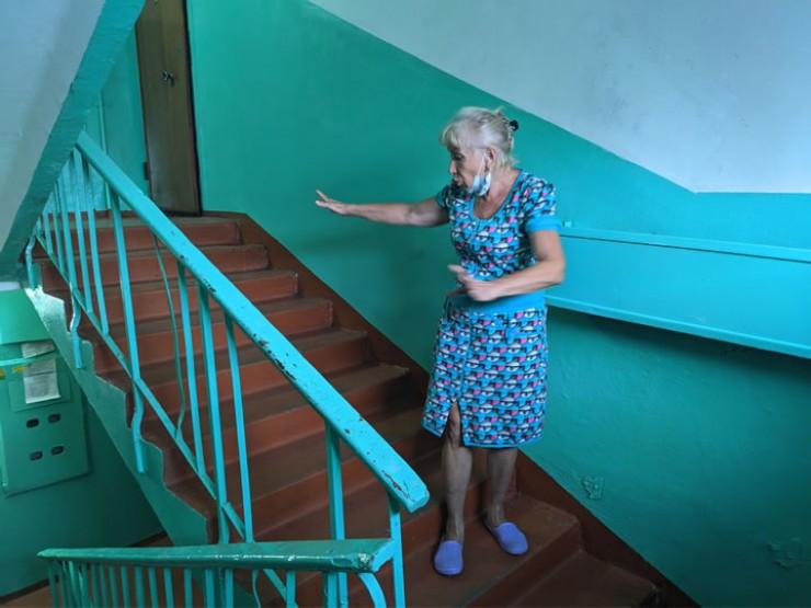 Соседка убитых Татьяна Гусева показывает место, где произошла трагедия.  По ее признанию, после случившегося у нее каждый раз немеют ноги, когда она выходит на лестницу