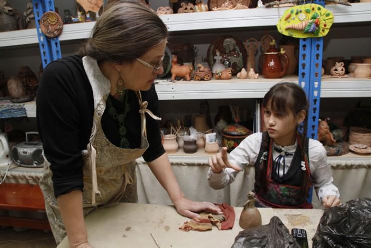 Мастер Елена Геннадьевна Майновская и шестиклассница Маша обсуждают,  какой длины должна быть указка у подарочной фигурки учительницы