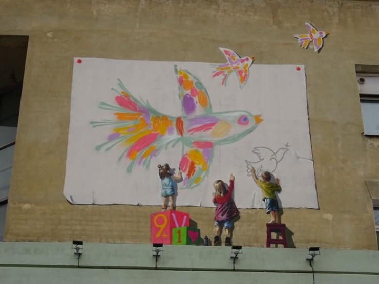 Это граффити на одном из корпусов Ивано-Матренинской детской больницы удивляет иркутян уже почти год. Всякий, кто впервые попадает в больницу, невольно замечает рисунок и на минуту останавливается — картина выполнена так реалистично, что в первый момент кажется, что это настоящие дети, стоя на козырьке, рисуют на огромном полотнище. Работа выполнена благотворительным фондом «Я Волонтер» в рамках проекта «Играя, выздоравливай». А впереди у фонда еще много задумок, в том числе оборудование комнаты психологической помощи мамам, чьи дети оказались в отделении патологии новорожденных