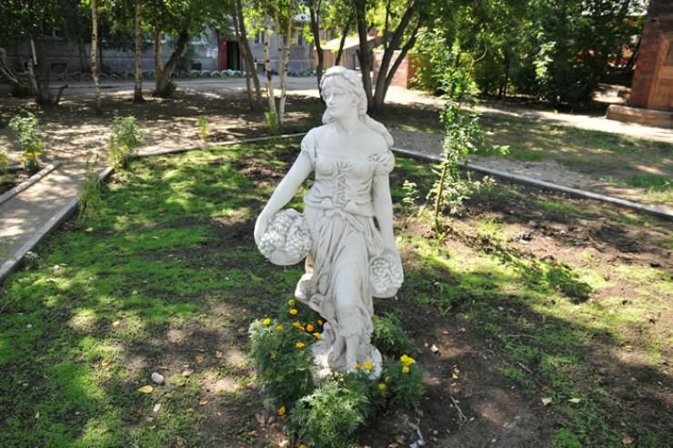 Иркутяне помнят, как  в 2009 году в этом дворе на улице Декабрьских Событий, 76, появилась скульптура миниатюрной девушки с двумя корзинами винограда. Установили ее сотрудники местного ЖЭКа. Около  5 лет статуя украшала двор, пока ее не сломал 25-летний местный житель. «Это было на моих глазах около шести лет назад! — рассказала «Пятнице» иркутянка Валентина. — Пьяный сосед из 72-го дома налетел на скульптуру  и отломил ей голову!  Мы даже сделать ничего не успели». Сломанную фигуру демонтировали,  а на ее месте появился детский городок, который очень радует местную ребятню. Ну а девушка  с виноградом,  к сожалению, существует теперь только на старых фотографиях и в памяти иркутян