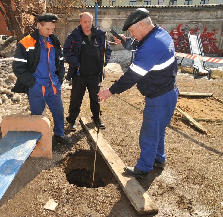 Провал в одном из дворов Иркутска. Коммунальщики замеряют его глубину. Как оказалось, здесь был подвал старого дома