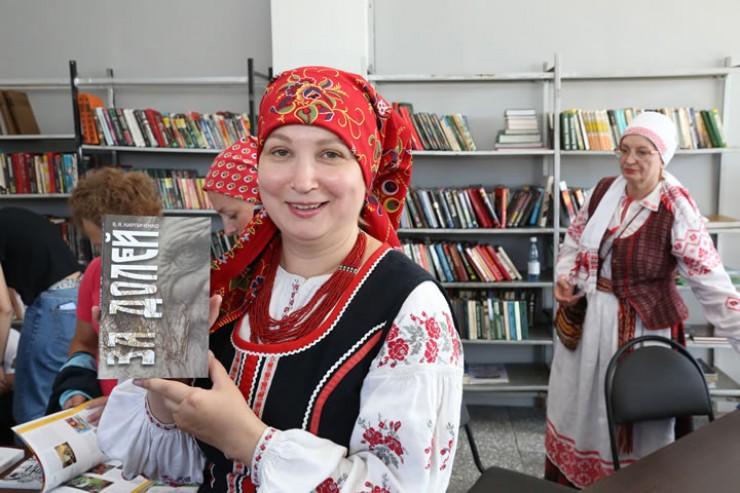 Председатель Иркутского товарищества белорусской культуры имени Яна Черского Алёна Сипакова демонстрирует книгу Виталия Кирпиченко