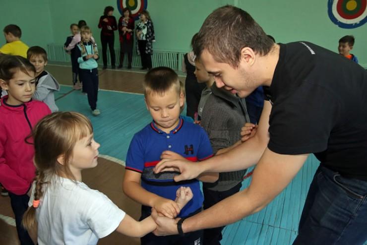 Призёр мирового чемпионата по карате Константин Верхозин показывает  первоклашкам, как правильно вырваться из захвата