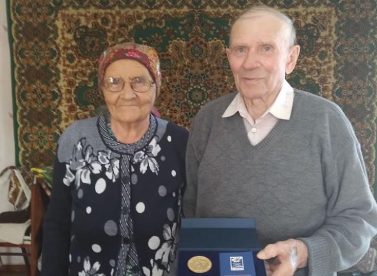 На просьбу сделать фото для газеты Макар Кузьмич обнимает супругу: через десятилетия Гусляковы смогли пронести любовь и трепетное отношение друг к другу.