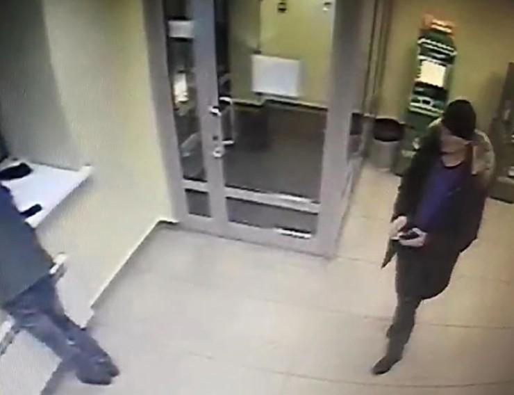 На фото с камер видеонаблюдения, установленных в операционном зале банка, — подозреваемый в хищении телефона у заснувшего посетителя. Ему 25—35 лет, выше среднего роста, нормального телосложения. Был одет в удлиненный пуховик темного цвета с капюшоном с меховой опушкой, фиолетовый пуловер с эмблемой на левой груди, вязаную черную шапку, серые брюки, классические ботинки. Если вы его узнали, сообщите в полицию