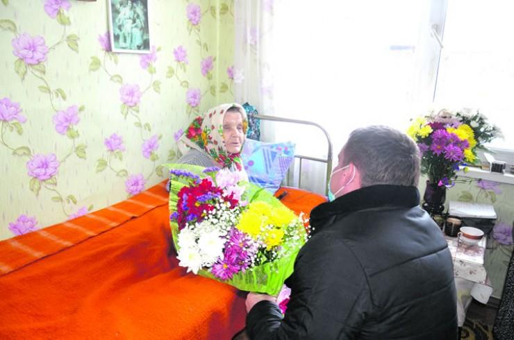 Анафью Васильевну поздравляет со 100-летием мэр Чунского района Николай Хрычов