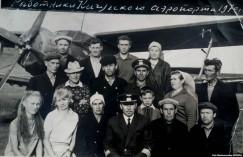 Владимир Иннокентьевич Прокопьев (в первом ряду в центре) с сотрудниками аэропорта Качуга в 1970 году. На заднем плане — самолёт Ан-2. Прокопьев закончил свою карьеру пилотом Ту-104 — одного из первых в мире реактивных самолётов гражданской авиации