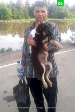 На руках у Игоря Рудина спасённые кот Барсик и щенок по кличке Тарзан