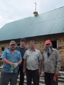 Прихожане как заправские строители возводят небольшой временный храм
