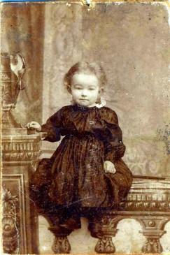 Фотография 1903 года. Снимок сделан в одном из фотосалонов Нижнеудинска. Двухлетняя малышка в ситцевом платье с пышной юбочкой и в аккуратных кожаных ботиночках — Валя Сбитнева. Она прожила долгую жизнь. Вырастила сына, дождалась внуков и вырастила правнуков