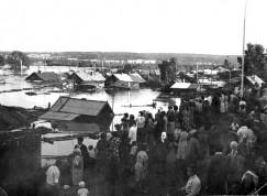 На фото — наводнение в Тулуне в конце июля 1980 года. Река Ия вышла из берегов, поднявшись почти на десять метров. Старожилы помнили наводнение 1937 года, но так высоко тогда вода не поднялась. Четыре года спустя, в июле 1984-го, случилось наводнение, которое затронуло не только Тулунский, но и Зиминский, Нижнеудинский и Чунский районы. Власти приняли решение о строительстве дамбы на реке Ие. 22 года все было относительно спокойно, но 13 лет назад, летом 2006 года, на город обрушилось сразу два наводнения: в июне и июле. Существующая дамба была серьезно разрушена, а строительство новой растянулось на несколько лет